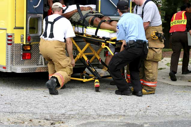 A man being lifted into an ambulance.